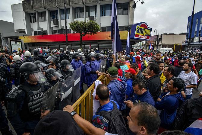 Bajo una fuerte presencia policial, manifestantes se congregan en el exterior de Asamblea Legislativa de Costa Rica para protestar por la polémica reforma fiscal.