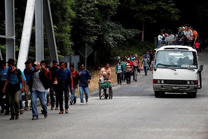 MIGRACIÓN. Nery Maldonado (en silla de ruedas), empujado por su amigo Omar Orellana (atrás), migra el martes 16 de octubre de 2018 junto con la caravana de hondureños que espera llegar a Estados Unidos y que ahora continúa su camino por Esquipulas, Guatemala