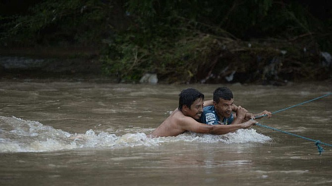 MIGRACIÓN. Los inmigrantes unieron dos pedazos de cuerda y lograron tensarla en el punto más estrecho. Dos hombres sostenían un extremo del lado de El Salvador y otros dos del lado de Honduras.