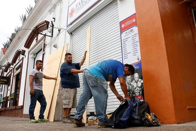 CLIMA. Habitantes protegen con madera la puerta de un negocio, el lunes 22 de octubre de 2018, ante la llegada del huracán Willa, en la ciudad de Puerto Vallarta de México