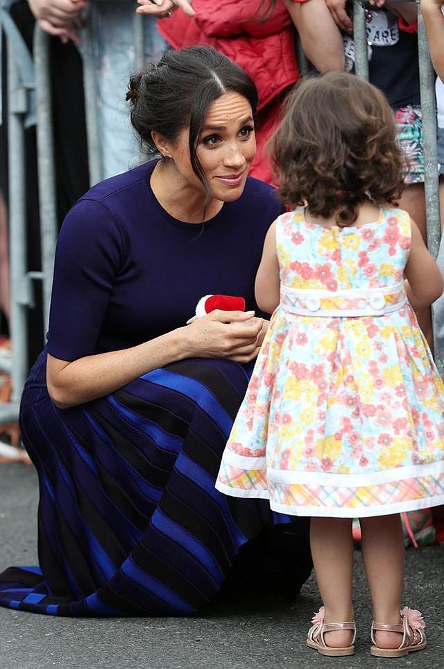 NUEVA ZELANDA. La duquesa Meghan de Sussex (i) saluda a una niña durante una visita a los jardines de Rotorua
