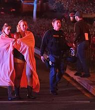 ESTADOS UNIDOS - Dos mujeres envueltas en una sábana abandonan el área del tiroteo cerca del bar Borderline en la localidad de Thousand Oaks, California. Al menos 12 personas han muerto en este tiroteo perpetrado por un individuo aun sin identificar, que también ha sido encontrado muerto en el interior del bar.