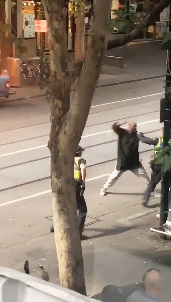 Captura de vídeo que muestra a un hombre armado con un cuchillo mientras se enfrenta a los agentes después de atacar a varias personas en la calle Bourke de Melbourne