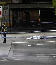 El cadáver de una víctima yace sobre el asfalto después de que un hombre armado con un cuchillo atacase a varias personas en la calle Bourke de Melbourne (Australia), hoy, 9 de noviembre de 2018