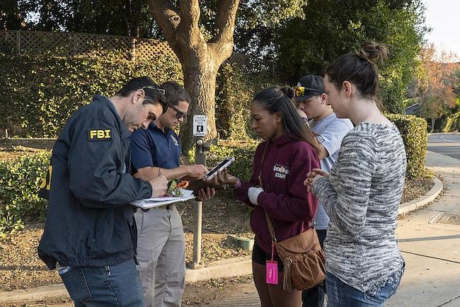 Jasmine Alexander, de 25 años, habla con un agente del FBI el viernes para recuperar su auto, que dejó cerca de Borderline Bar and Grill en Thousand Oaks, California. Alexander estaba en el bar el miércoles durante el tiroteo en masa. Se lastimó la mano izquierda mientras salía por una ventana.