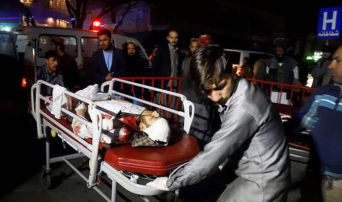 TRAGEDIA. Miembros de los servicios de emergencia transportan en camilla a un herido tras un ataque suicida en Kabul, Afganistán