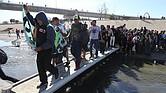 CARAVANA. Grupos de personas tratan de cruzar hoy, la garita El Chaparral, de la ciudad de Tijuana, en el estado de Baja California