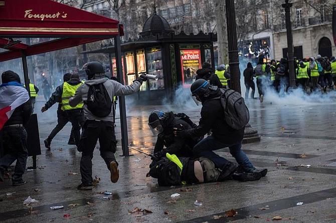 PROTESTA. La policía francesa arresta a un hombre durante una manifestación de chalecos amarillos en París, Francia, el 8 de diciembre de 2018