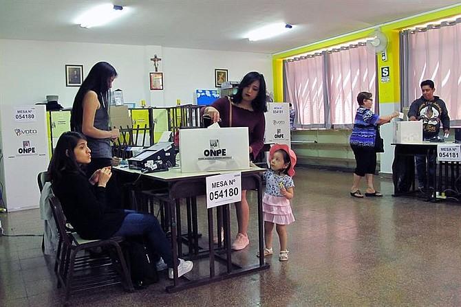 ELECCIONES. Una mujer acompañada de una niña vota el domingo 9 de diciembre, en un colegio electoral de Lima