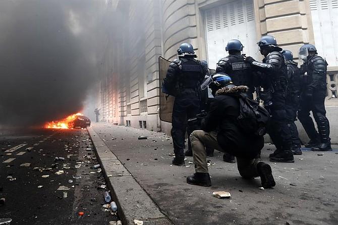 FRANCIA. Las fuerzas policiales de Rench están cerca de un coche en llamas cerca de la Avenida Marceau, durante la manifestación en París