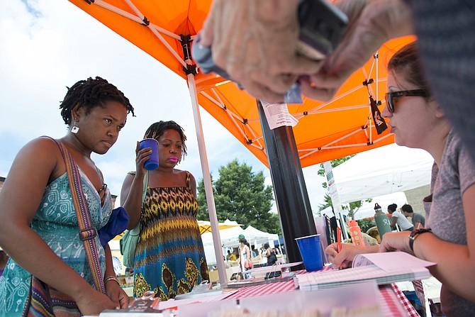 Jasmine Joseph-Morris, (izq) y Kinda Latese Clifford habla con un empleado de Fresh Farm Markets en Washington sobre programas de asistencia pública. FOTO: Washington Post photo by Linda Davidson.