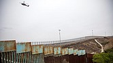 FRONTERA. Integrantes de la caravana migrante de centroamericanos son vistos junto al muro fronterizo, el 5 de diciembre, en la ciudad de Tijuana