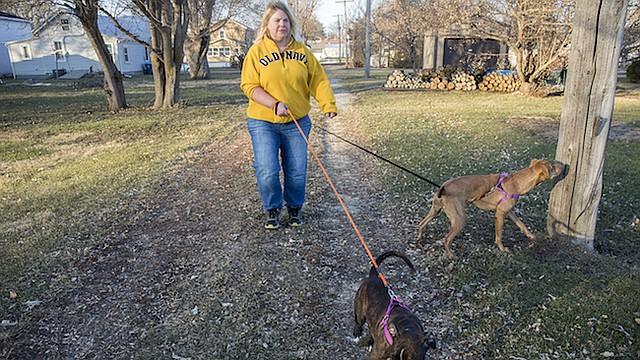 """Danette Lake pasea a sus perros, Zoe and Chloe, en su vecindario, en una zona rural de Iowa, en diciembre. Un año después de haber tenido su cirugía de reemplazo de rodilla, dijo que siente un """"dolor constante""""."""
