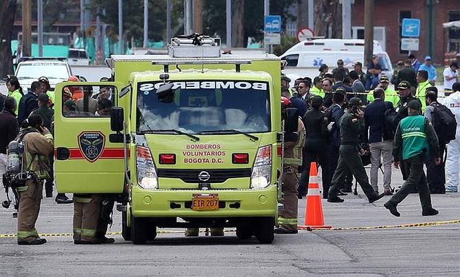 TERRORISMO. Miembros del cuerpo de Bomberos Voluntarios de Bogotá trabajan en el lugar donde un carro bomba causó una explosión este jueves en la Escuela General Santander de la Policía en Bogotá