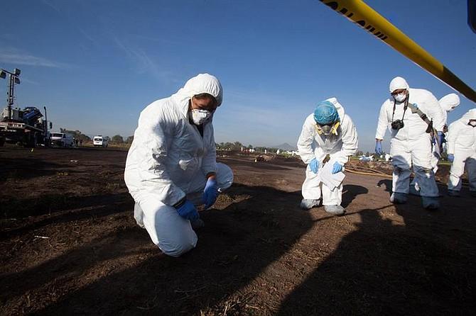 MÉXICO. Expertos forenses registran la zona cerca de una toma clandestina de gasolina de Petróleos Mexicanos (Pemex) que explotó este sábado, en Tlahuililpan, Hidalgo