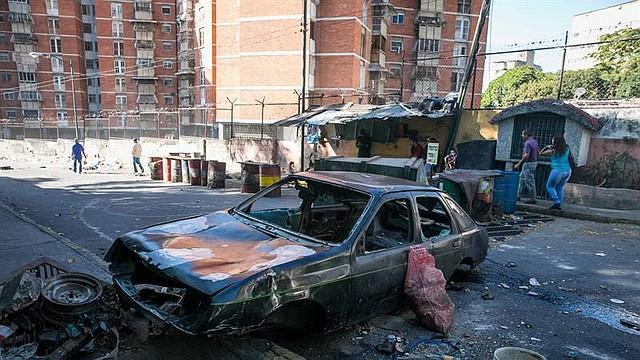 CARACAS. Restos de un vehículo incendiado en una calle donde hubo protestas este martes en Caracas