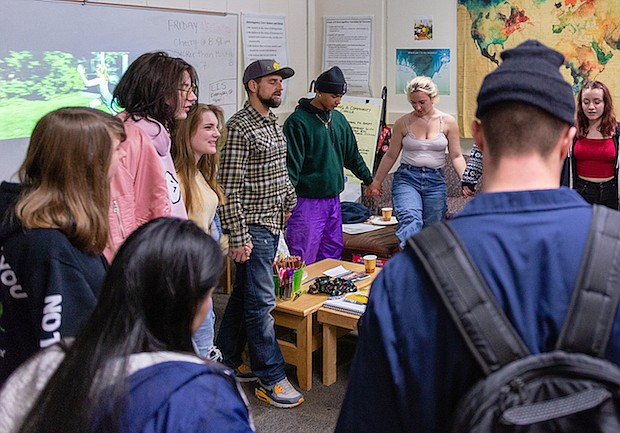 Estudiantes se toman las manos en círculo antes que termine el día escolar. Los estudiantes se reúnen a diario con consejeros y participan de programas de apoyo diseñados como Alcohólicos Anónimos.