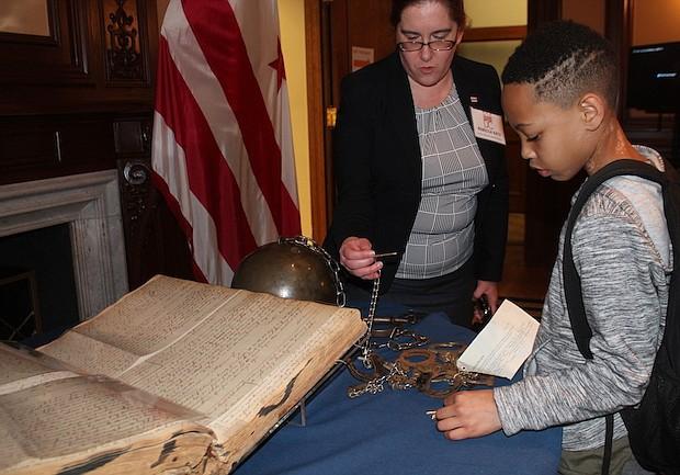 Historia. Este niño mira las esposas y un grillete que se usaban para encadenar a los esclavos.