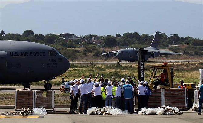 CRISIS. Trabajadores descargan las ayudas del primero de tres aviones de carga C-17 de la Fuerza Aérea de Estados Unidos y celebran el aterrizaje del segundo avión este sábado en el aeropuerto Camilo Daza de Cúcuta