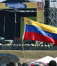 SOLIDARIDAD. Una bandera venezolana ondea frente al escenario del concierto Venezuela Aid Live este viernes, en el puente fronterizo de Tienditas, en Cúcuta