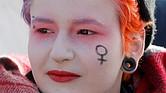 Una mujer con el símbolo femenino pintado sobre su rostro acude a una concentración en apoyo del Día Internacional de la Mujer, este viernes en San Petersburgo