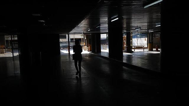 Una persona camina por un parqueadero sin luz debido a un apagón, en Caracas