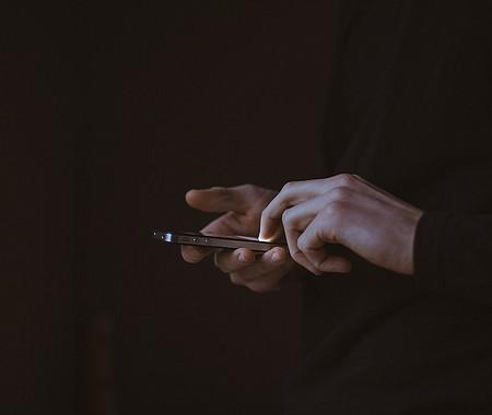 Foto de referencia de un teléfono celular en manos de una persona