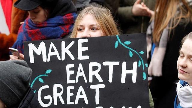 """LETONIA. Una estudiante sostiene una pancarta en la que puede leerse ''Haced la Tierra grande de nuevo'', durante una manifestación con motivo de la huelga escolar convocada por el movimiento """"Jóvenes por el Clima"""" en todo el mundo para exigir a los políticos que adopten medidas en la lucha contra el cambio climático"""