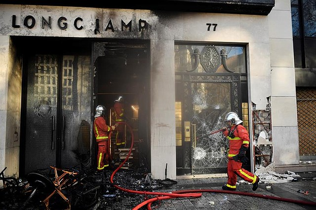 """FRANCIA. Un bombero apaga una tienda quemada de Longchamp durante los enfrentamientos con los manifestantes de los """"Gilets Jaunes"""" (chalecos amarillos) en medio del humo en los Campos Elíseos durante la manifestación del """"XVIII Acto"""""""