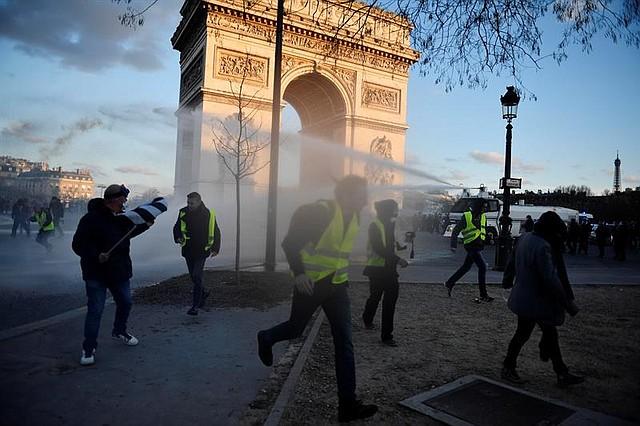 """FRANCIA. Manifestantes de los """"Gilets Jaunes"""" (chalecos amarillos) se paran entre el humo de los Campos Elíseos durante la manifestación del """"XVIII acto"""" (la decimoctava protesta nacional consecutiva de un sábado) en París."""