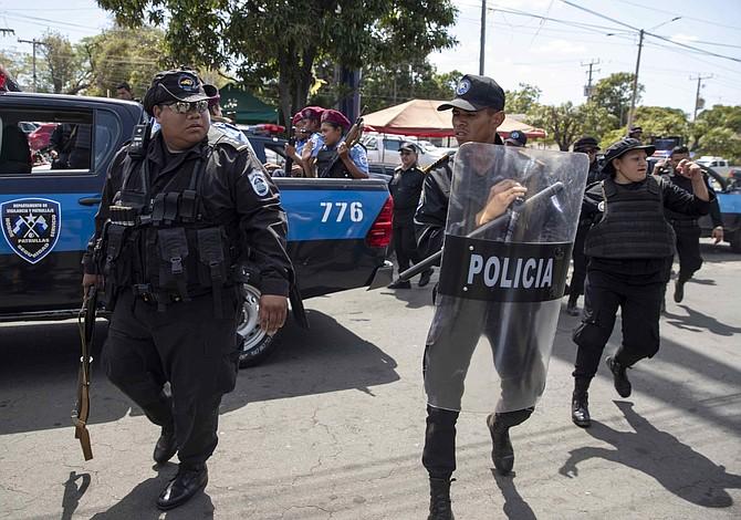 MANAGUA. Miembros de la Policía Nacional realizan un cordón de seguridad frente a los medios de comunicación durante una manifestación contra Ortega