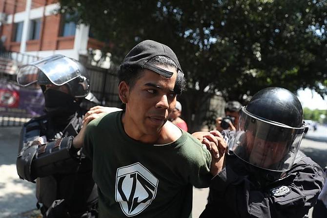 Bryan Martínez es detenido por la unidad antimotines de la policía luego de finalizar una marcha este miércoles en San Salvador.