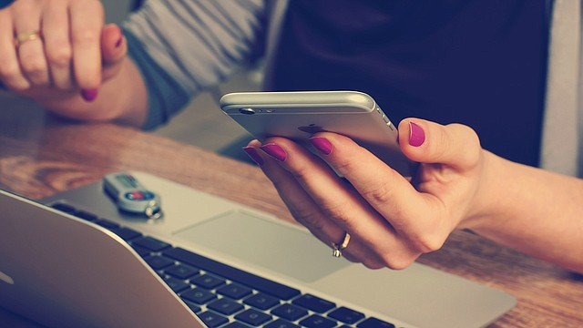 TECNOLOGÍA. Foto de referencia de una mujer mientras usa su teléfono celular y una laptop