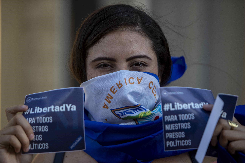 PROTESTA. Una joven con una bandera de Nicaragua envuelta en la cara participa de una manifestación en contra de Daniel Ortega el sábado 16 de marzo, en Managua.