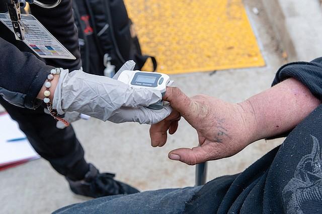 La asistente médica Negeen Farmand, de Sabam Community Clinic, chequea los signos vitales de Jennifer Millar en el campamento de personas sin techo en la autopista de Hollywood.