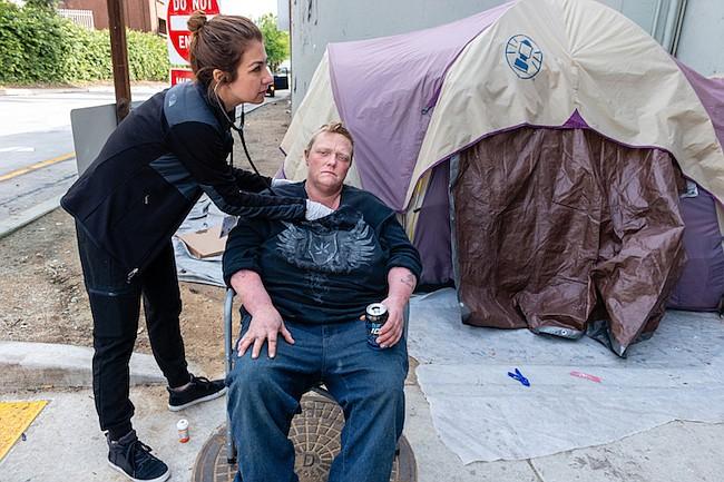 """La asistente médica Negeem Farmand asiste a Jennifer Millar. """"Es difícil que estas personas vayan a las clínicas. Desconfían del sistema de salud"""", dijo."""
