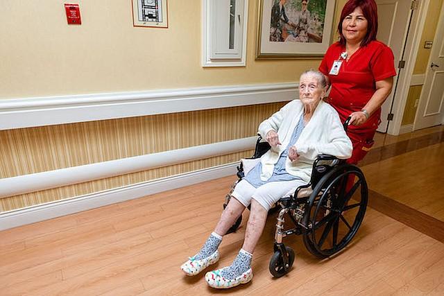 Una enfermera del Coventry Court Health Center en Anaheim, California, lleva a Neva Shinkle a su habitación para bañarla con un jabón especial para ayudar a combatir las infecciones.