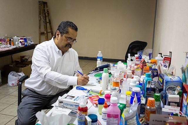 El doctor José Manuel de la Rosa escribe una receta en una clínica improvisada en un viejo depósito en El Paso.