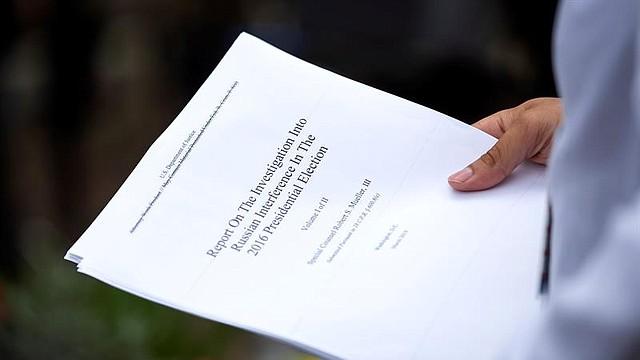 POLÍTICA. Un periodista sostiene una copia impresa de la versión redactada de la declaración del fiscal especial Robert Mueller este jueves, en Washington, Estados Unidos