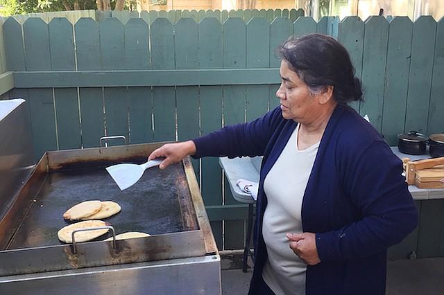 María Contreras prepara pupusas para el negocio de su familia de venta de comida. El objetivo es ayudar a reemplazar los ingresos de su hermano, un trabajador de la construcción que está detenido en el Adelanto ICE Processing Center, en el sur de California, desde junio pasado.