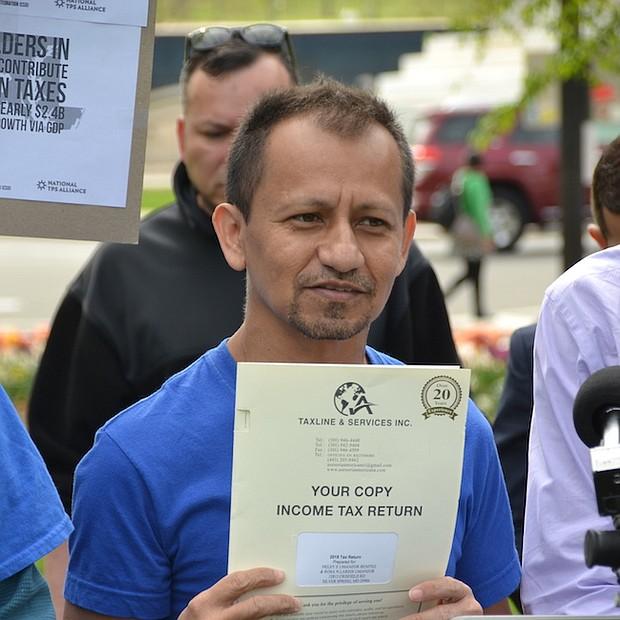 APORTE. Un beneficiario del TPS acudió con la copia de su declaración de impuestos a una manifestación afuera del Capitolio.