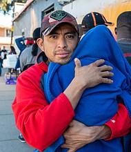 José Manuel Salinas, de Acapulco, Guerrero, sostiene al bebé de su amigo mientras espera en la fila para que lo vea una enfermera. Salinas dijo que le tomó cerca de un mes de caminata y hacer auto stop para llegar a la ciudad fronteriza de Tijuana. Lleva dos semanas luchando contra un resfriado.