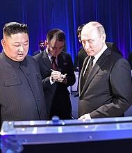 RUSIA. El líder norcoreano, Kim Jong-un (izq), y el presidente ruso, Vladímir Putin (c), intercambian regalos durante una recepción posterior a su reunión, este jueves, en el campus de la Universidad Federal del Lejano Oriente, en la isla de Russki, Vladivostok