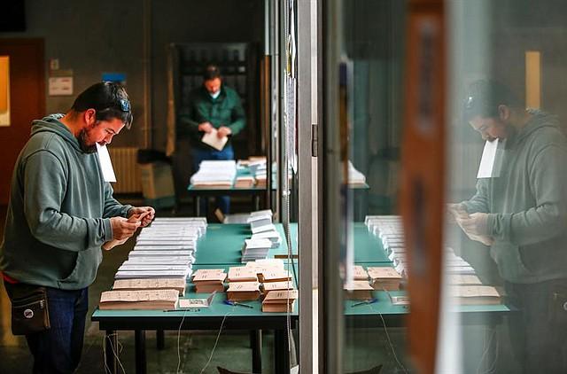 ESPAÑA. Ciudadanos buscan su papeleta de voto en un colegio de Barcelona. Los colegios electorales han abierto sus puertas a las 09:00 horas para recoger el voto de los casi 36,9 millones de electores que decidirán en los comicios generales el reparto de los 350 escaños del Congreso de los Diputados y los 208 del Senado durante la próxima legislatura votación