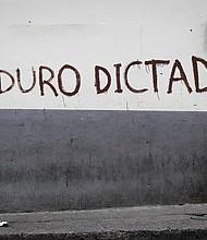 VENEZUELA. Una persona camina frente a una pared pintada contra Nicolás Maduro en Caracas