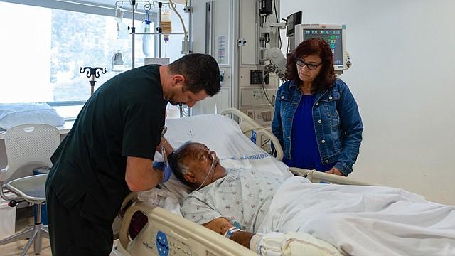 """Maria Torres visita a su hermano Felipe Luna. Luna fue trasladado a Los Angeles County+USC Medical Center luego de ser arrollado por un auto y sufrir heridas en la cabeza. """"Lo único que tenía con él era una tarjeta de un banco y un recibo"""", dijo Torres. """"No tenía una identificación, pero fue bueno que al menos tenía eso en el bolsillo """"."""