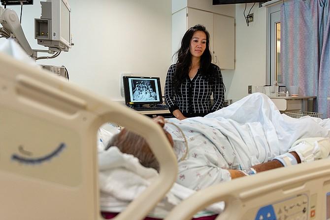 Lenh Vuong, trabajadora clínica social de Los Angeles County+USC Medical Center, visita a un paciente que ingresó sin nombre y que recientemente fue identificado.