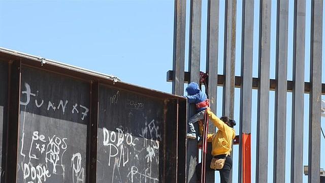 FRONTERA. Una mujer ayuda a su hijo a trepar la valla fronteriza que divide a México y Estados Unidos el miércoles 5 de junio, en el tramo de Puente Negro, en Ciudad Juárez