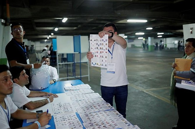 ELECCIONES. Un fiscal de la mesa electoral muestra una papeleta de votación marcada en Ciudad de Guatemala.
