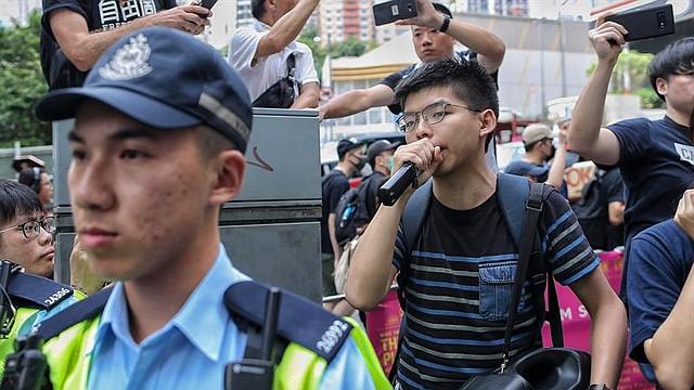 MUNDO. El líder estudiantil Joshua Wong (dcha) da un discurso a sus seguidores durante una manifestación convocada ante el Departamento de Justicia en Hong Kong